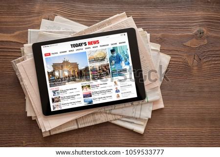 Tablet with news website on stack of newspapers. All contents are made up. #1059533777