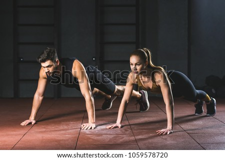 Sportswoman and sportsman doing push ups in gym in sports hall #1059578720
