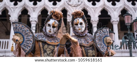 Venice Italy, February 2018. Two women in traditional costume and painted masks, with decorated fans, standing in front of the Doges Palace during the Venice Carnival #1059618161