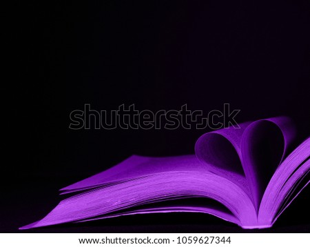 Pages of a book curved into a heart shape. Ultra violet color. Copy space. #1059627344