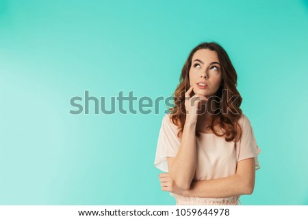 Portrait of a pensive young girl in dress standing and looking away at copy space isolated over blue background #1059644978