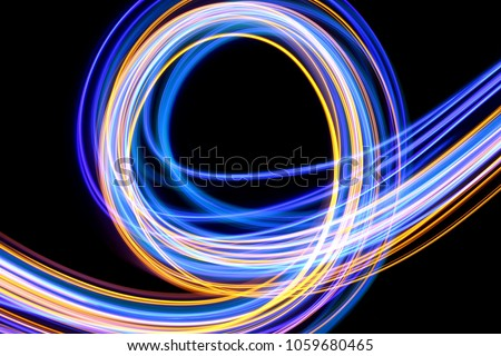 Blue and gold light painting photography, long exposure fairy lights curves and waves against a black background
