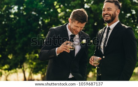 Groom and best man drinking and smiling during wedding party. Groom and groomsmen partying after wedding. #1059687137