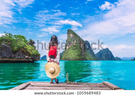 Traveler woman with backpack joy relaxing on floating wood bridge and looking Beautiful destination island, Panyee island, Phang nga bay, Travel Thailand, natural landscape Asia, Summer vacation trip #1059689483