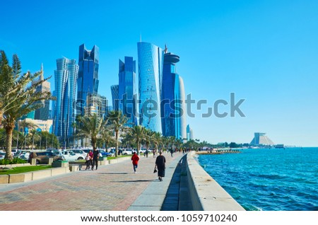 DOHA, QATAR - FEBRUARY 13, 2018: The Corniche promenade stretches along the glass skyscrapers of Al Dafna district and opens many nice views on the modern constructions, on February 13 in Doha. #1059710240