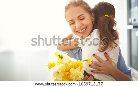 happy mother's day! child daughter congratulates mother and gives a bouquet of flowers to narcissus and gift #1059713177