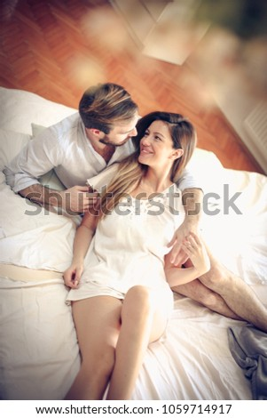 Happy young couple in bed. Space for copy. #1059714917
