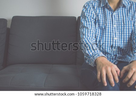 A man sitting on a sofa. #1059718328