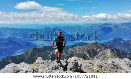 hiker smiling in fronto of the panorama of the lake of Como and lecco and resegone #1059721811