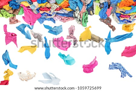 Separate clothing fall from a large pile of clothes on a white background #1059725699