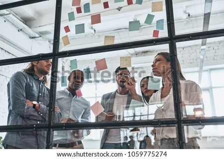 Hard choice to make. Group of young modern people in smart casual wear using adhesive notes while standing behind the glass wall in the board room            #1059775274