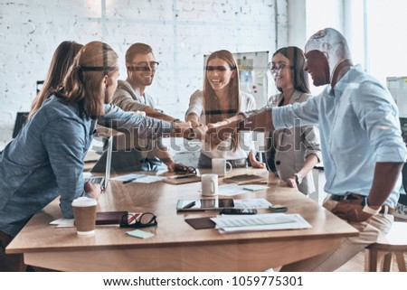 Great results. Group of business colleagues holding fists together in a symbol of unity while working behind the glass wall in the board room #1059775301