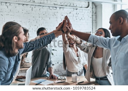 High-five for success! Diverse group of business colleagues giving each other high-five in a symbol of unity and smiling while working in the board room    #1059783524