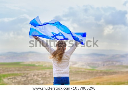 Little patriot jewish girl standing  and enjoying with the flag of Israel on blue sky background.Memorial day-Yom Hazikaron, Patriotic holiday Independence day Israel - Yom Ha'atzmaut concept #1059805298