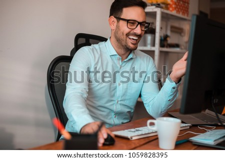 Job can be funny. Smiling handsome business man sitting in front of monitor. #1059828395