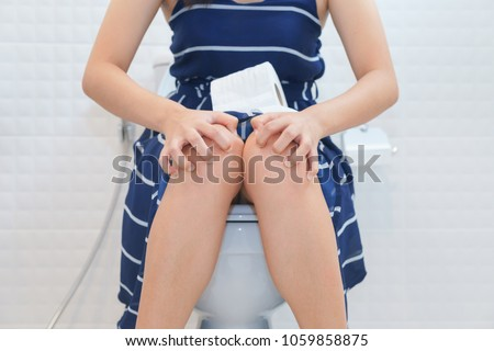 Woman sitting on toilet with toilet paper - constipation concept #1059858875