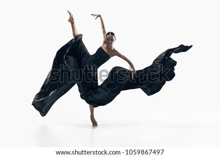 Modern ballet dancer exercising isolated in full body on white studio background. Ballerina or modern dancer in black silk dress dancing on white studio background. Caucasian model dancing barefoot Royalty-Free Stock Photo #1059867497
