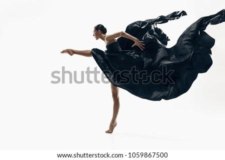 Modern ballet dancer exercising isolated in full body on white studio background. Ballerina or modern dancer in black silk dress dancing on white studio background. Caucasian model dancing barefoot Royalty-Free Stock Photo #1059867500