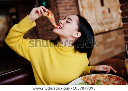Funny brunette girl in yellow sweater eating pizza at restaurant.  #1059879395