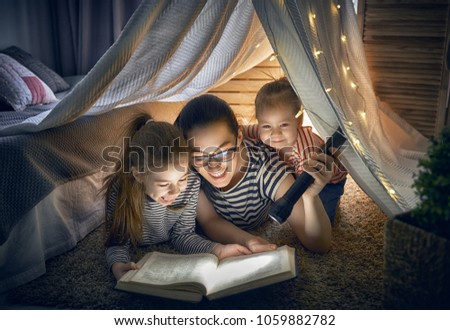 Family bedtime. Mom and children daughters are reading a book in tent. Pretty young mother and lovely girls having fun in children room. #1059882782