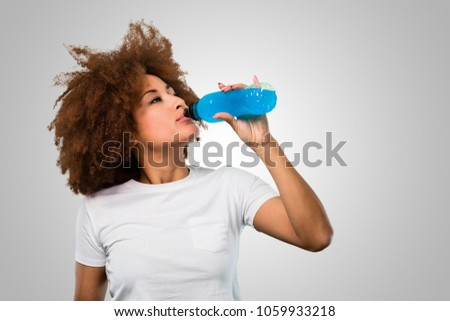 young fitness afro woman drinking an energy drink