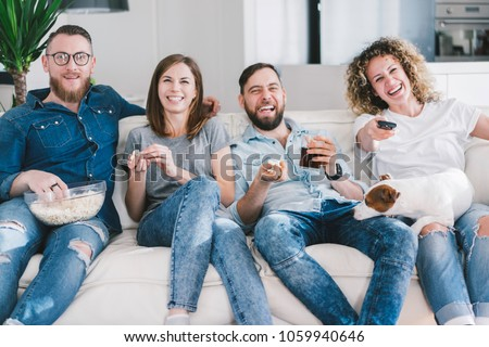 friends and thier lovely jack russel terrier dog spending day-off relaxing in front of tv in cozy living room and laughing together watching amusing tv-show. Young people having fun at their weekend. #1059940646