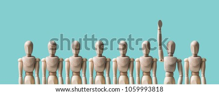 A group of wooden mannequins, one mannequin raises his hand. HR concept, human resources, volunteering. The character reports an answer, wants to apply for a job. Pastel background. #1059993818