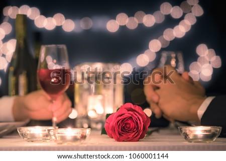 Romantic dinner date night. Focus on red rose. #1060001144