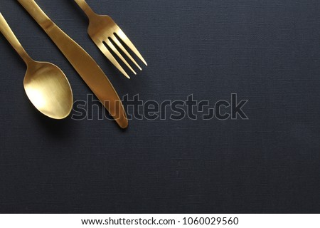Gold fork, knife and spoon frame against  open black copy space. Royalty-Free Stock Photo #1060029560