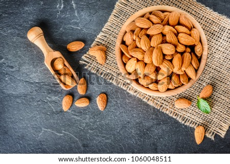 Top view of almonds on dark stone table with wood spoon or scoop. Almond in wooden bowl. Nuts freely laid on dark board. #1060048511