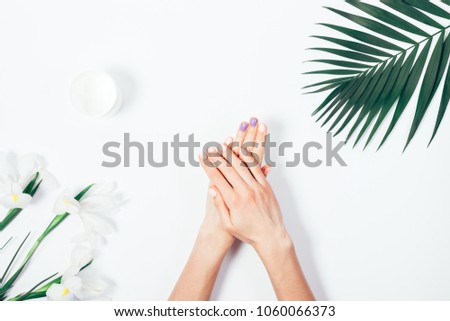 Top view woman putting nutritious cream on her hands on white background among jar of cosmetic cream, flowers and palm branch. Final stage of manicure: woman uses moisturizer for the skin. Copy space. #1060066373