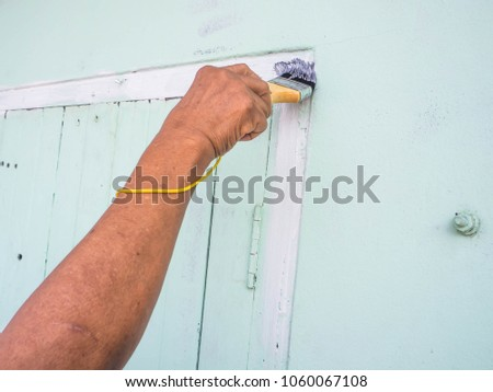 Asian female worker painted white color over a light green on a wooden window frame. #1060067108