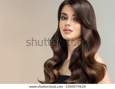Brunette  girl with long , healthy and   shiny curly hair .  Beautiful  model woman  with wavy hairstyle   .Care and beauty Royalty-Free Stock Photo #1060074626