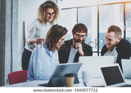 Teamwork concept.Young creative coworkers working with new startup project in modern office.Group of three people analyze data on desktop computer.Horizontal,blurred background Royalty-Free Stock Photo #1060077722