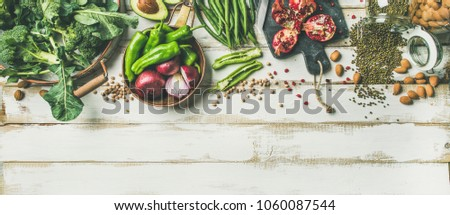 Winter vegetarian, vegan food cooking ingredients. Flat-lay of vegetables, fruit, beans, cereals, kitchen utencil, dried flowers, olive oil over white wooden background, top view, copy space #1060087544