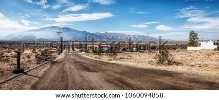 Deserted lonely empty road in San Felipe, Mexico, distant mountain with white summer clouds, few abandoned empty houses in the scorching heat, no cars or people, super wide panorama stitch, COVID-19 Royalty-Free Stock Photo #1060094858