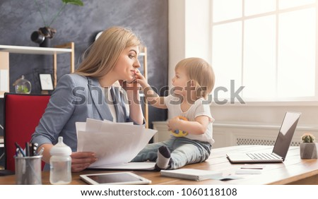 Happy beautiful business mom talking on smartphone and working with documents in office while her cute baby playing with toys. Business, motherhood, multitasking and family concept. #1060118108
