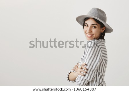 Attractive girlfriend posing to make new picture on vacation. Fashionable caucasian girl in stylish hat standing in profile and smiling broadly at camera, crossing hands and expressing sensuality