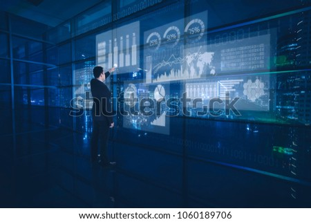 Male manager working with modern virtual technology in the office and touching virtual screen  #1060189706