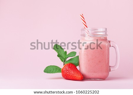 Strawberry smoothie or milkshake in mason jar decorated mint on pink table. Healthy food for breakfast and snack. #1060225202