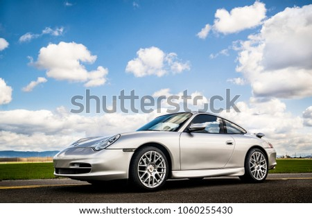 April 2, 2018 Eugene Oregon - A silver Porsche 911 body style 996 sits on an empty road under a sunny cloud filled sky near some green fields of grass. #1060255430