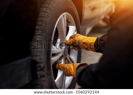Auto mechanic man with electric screwdriver changing tire outside. Car service. Hands replace tires on wheels. Tire installation concept. #1060292144