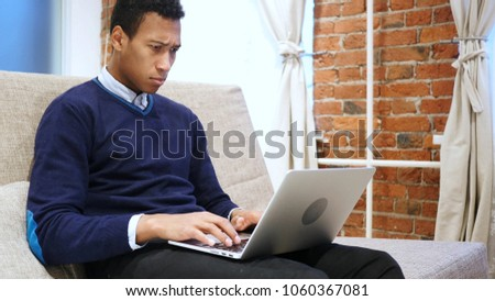 Tense African Man Working on Laptop, Home #1060367081