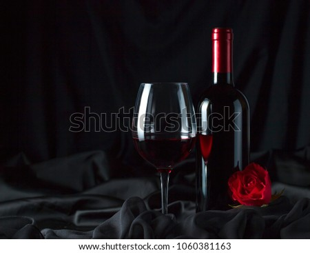Bottle and glass of red wine with black silk and red rose on black background. Copy space . #1060381163