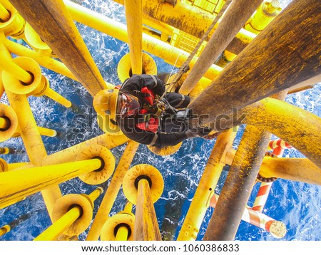 Male worker rope access  inspection of thickness offshore drill yellow oil and gas production petroleum pipeline. #1060386833