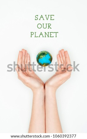 cropped image of woman holding earth model with sign save our planet isolated on white, earth day concept #1060392377