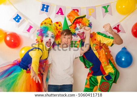 clown girl and clown boy at the birthday of a child. Party for children. Clowns try to cheer an adult boy #1060411718