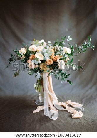 Beautiful modern wedding bouquet in peach and beige tones on dark grey background. Flower invitation card. Elegance wedding inspiration. Valentines day, proposal idea. #1060413017