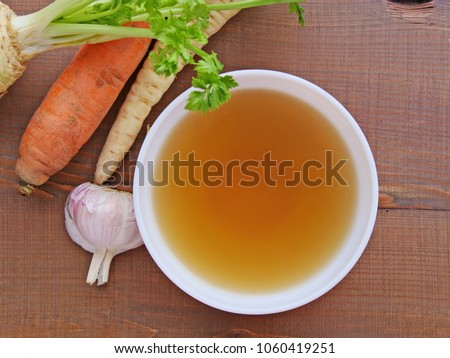 Clear beef broth, bone broth, bouillon in white bowl and vegetables on wooden table top view