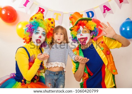 clown girl and clown boy at the birthday of a child. Party for children. Clowns and little girl show different emotions  #1060420799
